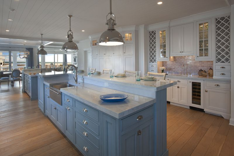 Raised eating area above large island with baby blue cabinets and stainless steel farmhouse sink.