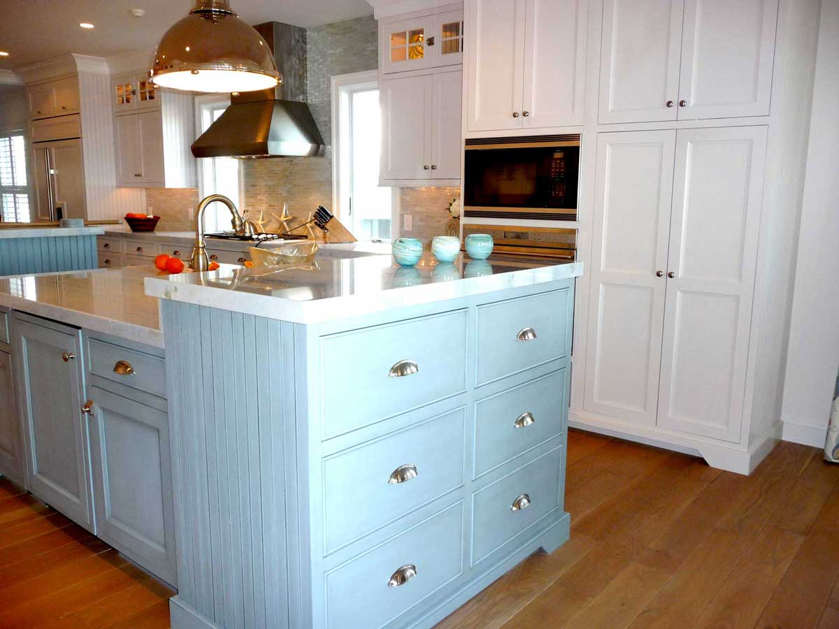 Wall cabinetry and baby blue cabinets provide extra kitchen storage and a place for microwave oven.