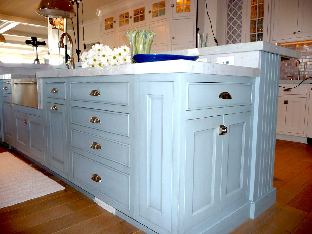 Baby blue cabinets pair well with light colored floors, white countertops, and white kitchen accents.