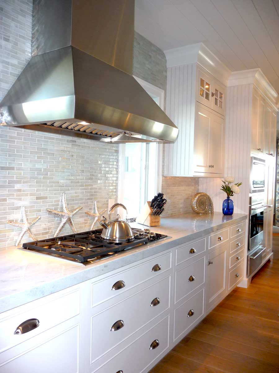 Range hood and Wolf stove complemented by custom pearlized back splash design and baby blue cabinets.