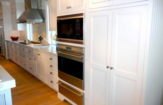 A warming drawer sits beneath a wall microwave and convection oven housed near baby blue cabinets.