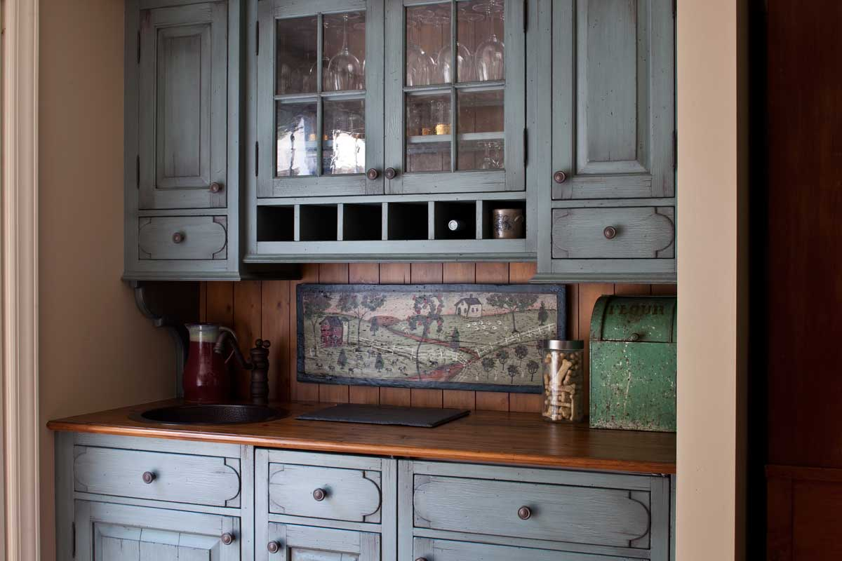 Traditional kitchen design with glazed white cabinets and a blue hutch