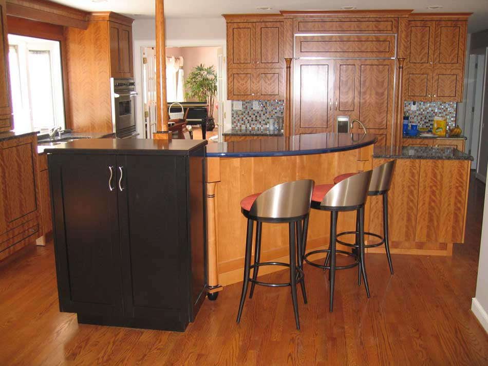 Cherry wood cabinetry for a contemporary kitchen design with a colorful kitchen backsplash and island seating