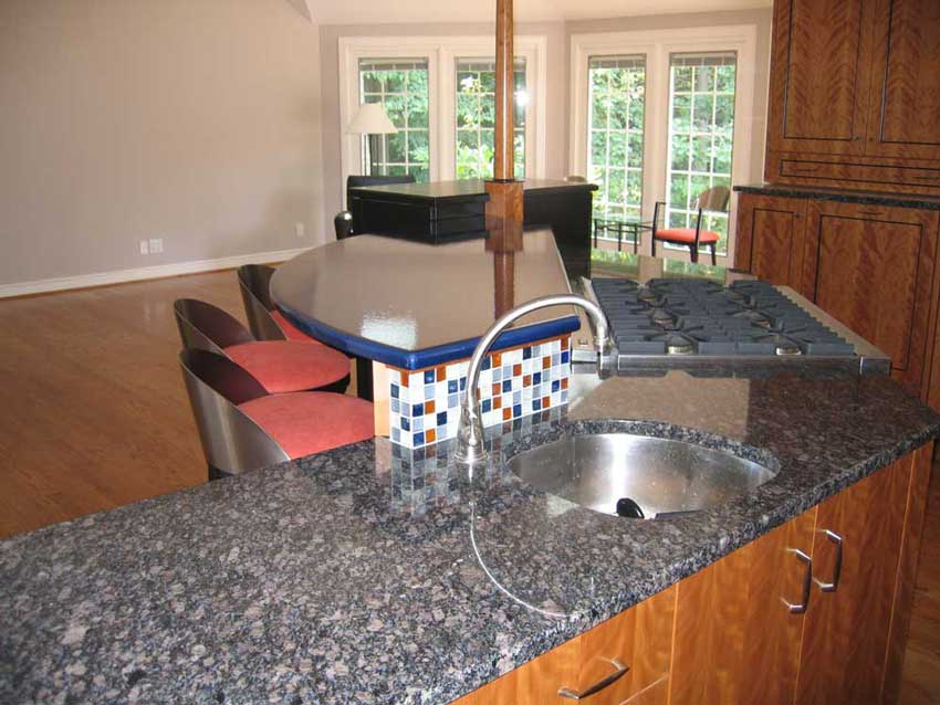 multi-level kitchen island with a granite countertop and a pyrolave countertop and a colorful kitchen backsplash