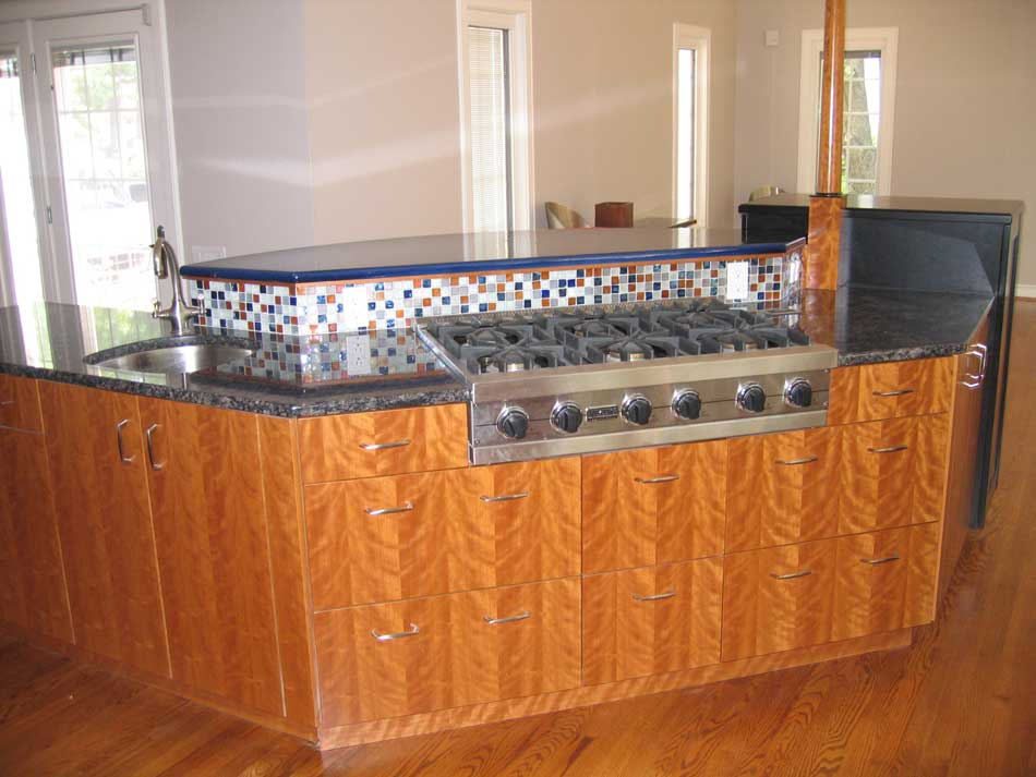 cherry wood kitchen island cabinets with a stainless steel cook top and a colorful kitchen backsplash