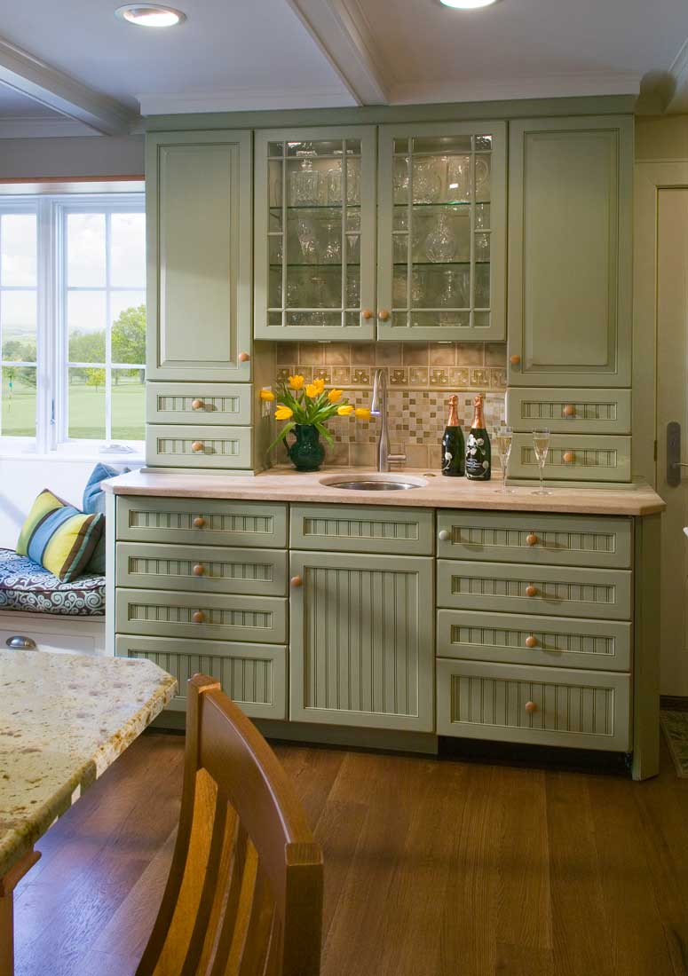 A light green kitchen hutch provides practical storage to an elegant kitchen inspired by the 1940's.