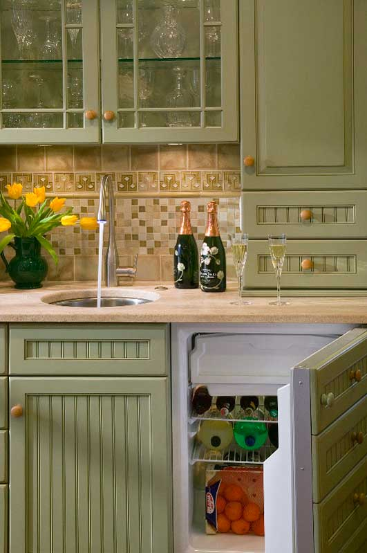 A hidden mini fridge inside the green kitchen hutch is concealed by wood cabinet drawers.