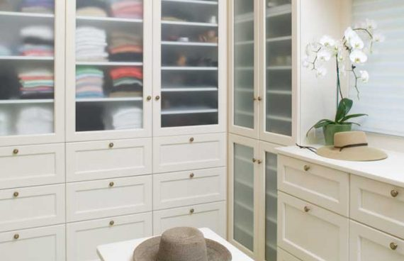 Womanu0027s Closet Of His Hers Closet Has White Cabinetry With Frosted Glass  And A Center Island
