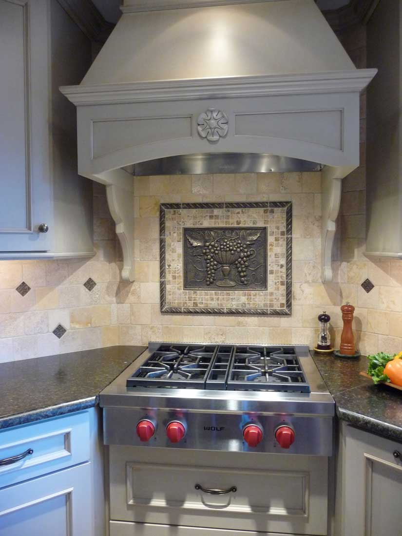 Stainless steel subzero and wolf 4 burner cooktop range with red knobs and custom range hood