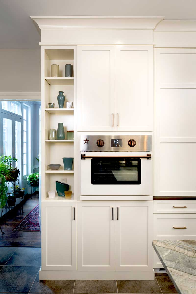 Tall white cabinets with kitchen copper accents including copper cabinet pulls and custom copper oven knobs