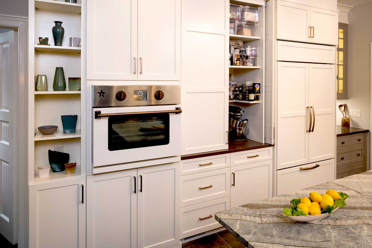 white cabinetry with copper cabinet hardware and hidden cabinet storage and a wooden panel refrigerator
