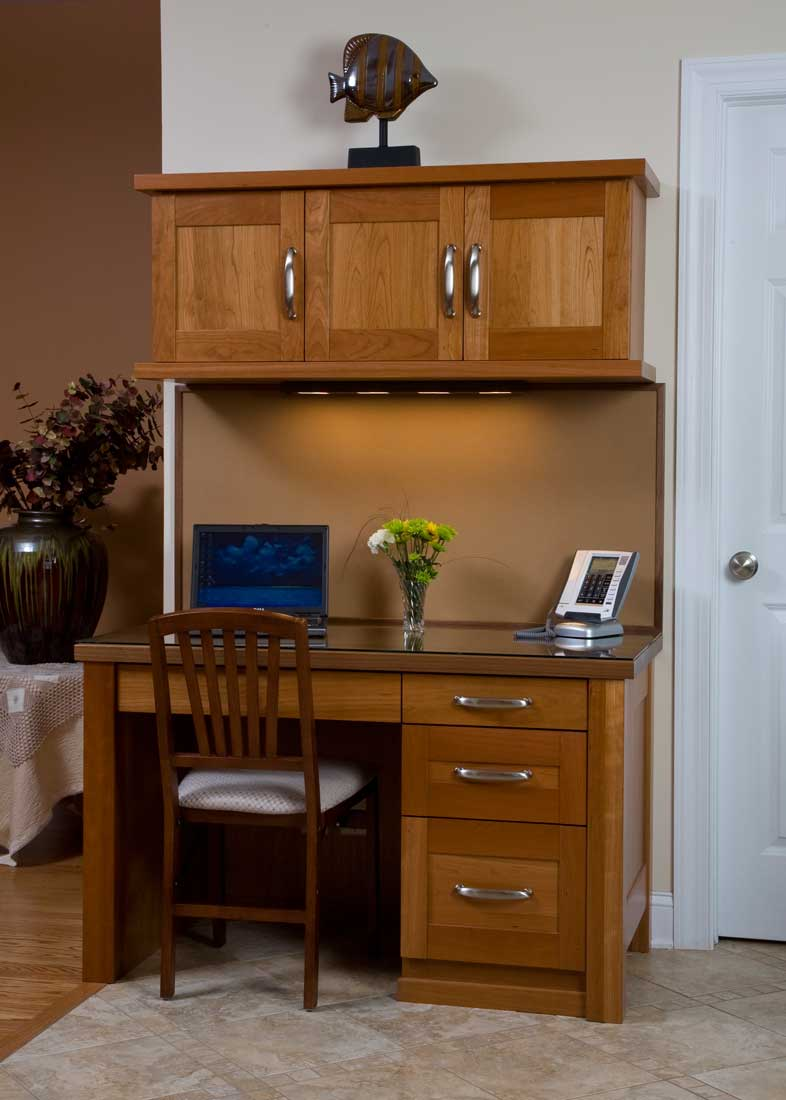 A light-colored, wooden contemporary style kitchen desk with optimal storage and under custom lighting features.