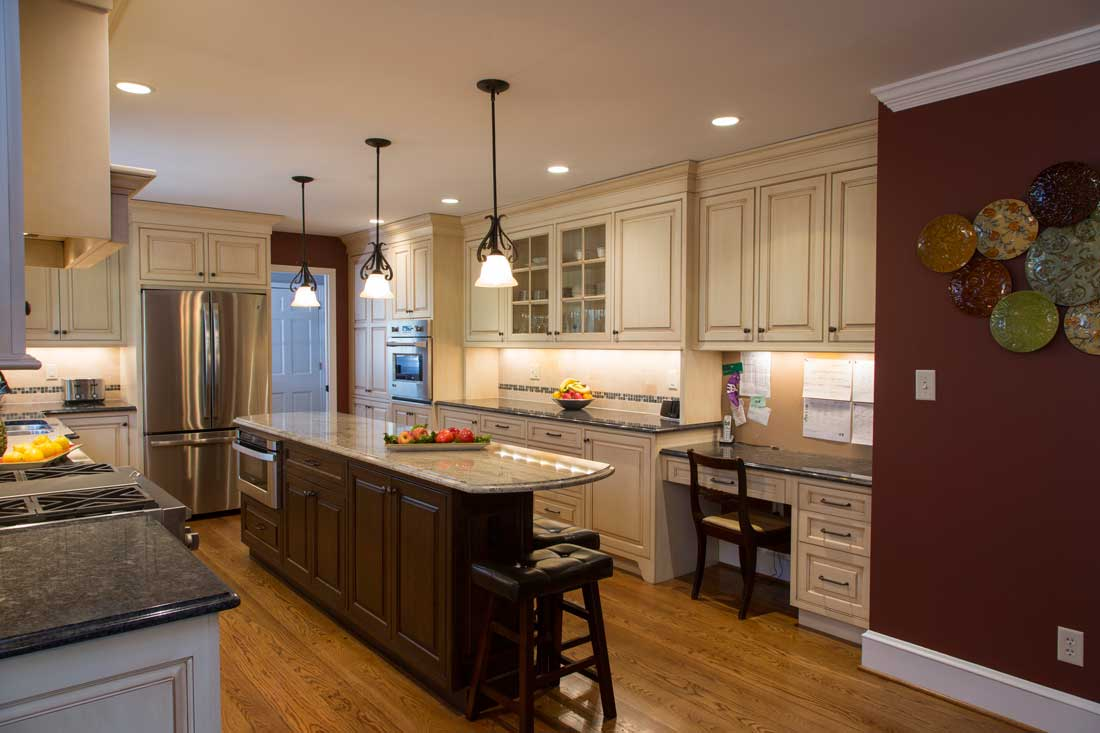 Maroon kitchen walls with dark wood kitchen island cabinets and off white perimeter kitchen cabinets