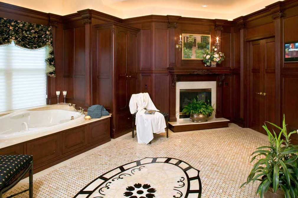 Large formal master bath design with dark wood cabinets and crown molding with a fireplace