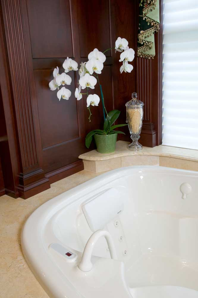 Large white bathtub decorated with flowers in a formal master bath design with dark wood cabinetry