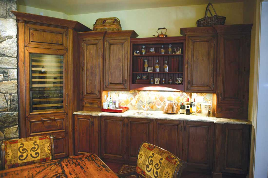 Renovated bar area includes mixed kitchen cabinet colors for a warm and inviting feel to space.