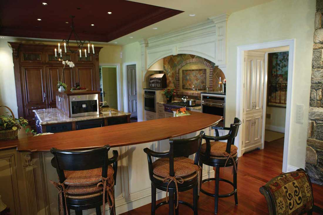 Combining Cabinet Colors in a breakfast bar area with wood countertops complete a traditional kitchen design.