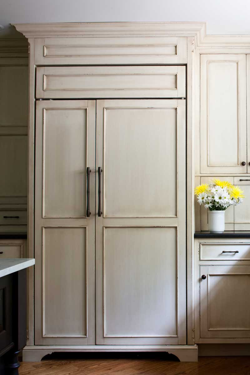 Sub Zero refrigerator concealed with wood panels in order to match the kitchen's off white cabinets.