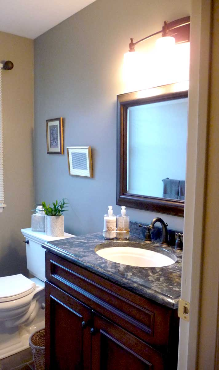 Powder Room with a single vanity sink and a vanity mirror with lighting and wall décor