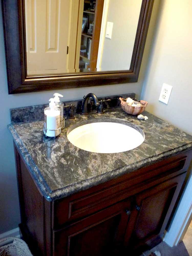 Single Vanity with One sink and Dark Wood Cabinets With a Matching Wood Frame Around Mirror