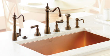 rohl faucet set in dark bronze with a soap dispenser, a removable spray and drinking faucet