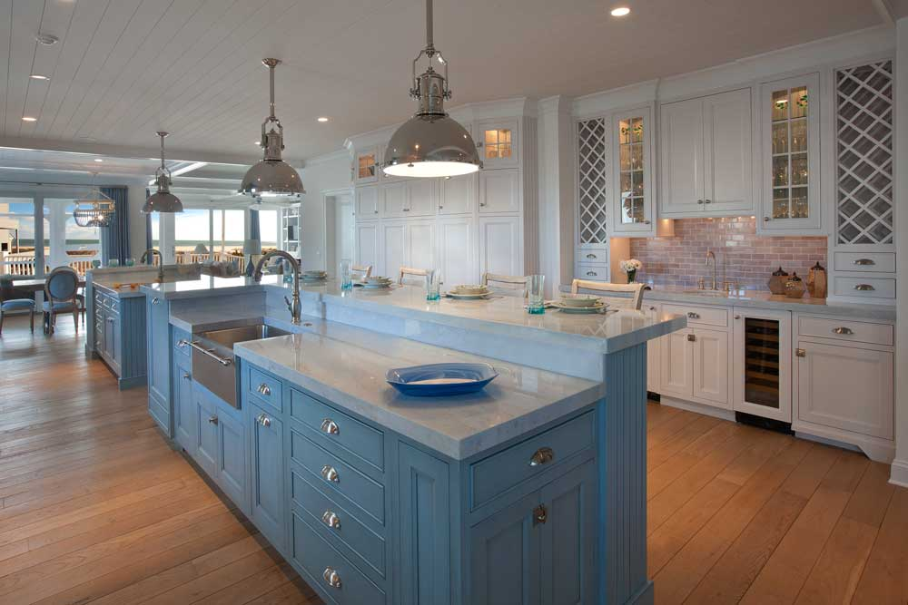 Raised eating area above large island with bayou blue cabinets and stainless-steel farmhouse sink.