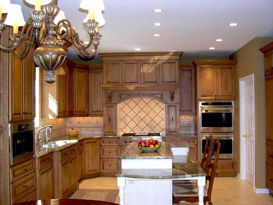 traditional kitchen with maple wood perimeter cabinetry and white island cabinets and stainless steel kitchen appliances