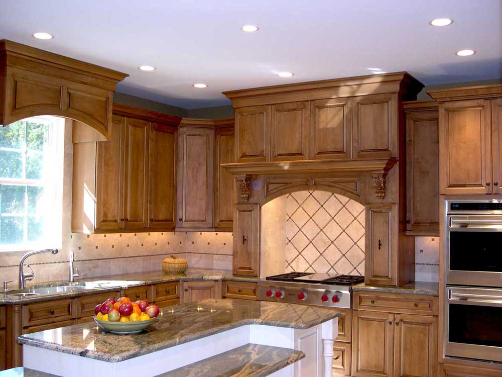 Stainless steel kitchen appliances in a traditional kitchen design with maple wood perimeter cabinets