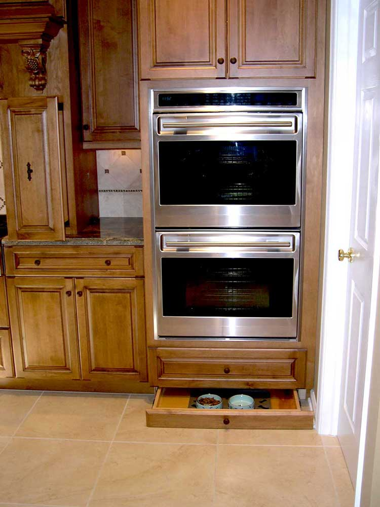 Maple wood cabinets with stainless steel kitchen appliances and wooden dog food storage cabinet under ovens