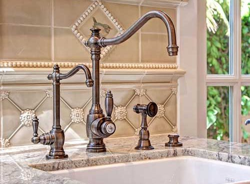 unique Waterstone faucets in a dark bronze color with a removable spray and a drinking faucet