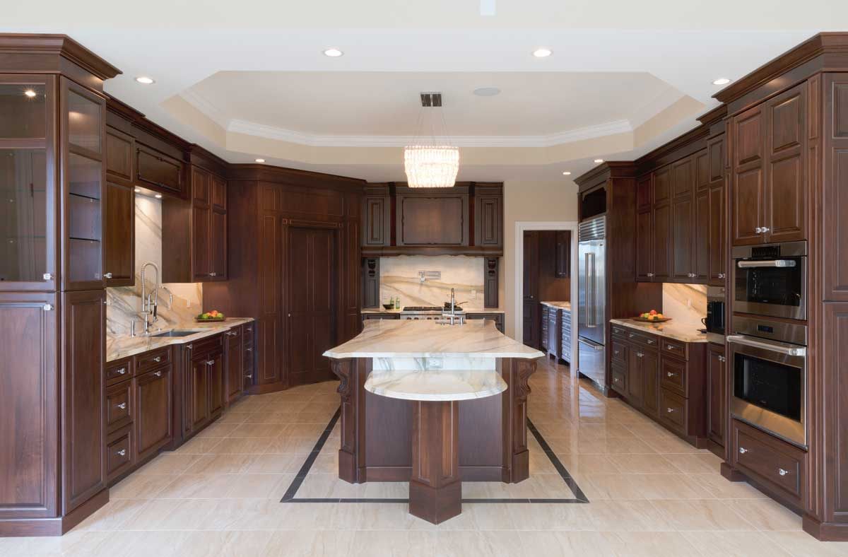 Large Traditional cocoa walnut kitchen design with a large kitchen island with a gold crystal chandelier