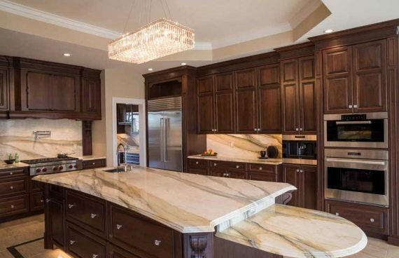 White brown kitchen with dark wood cabinetry and white countertops and island for a traditional kitchen
