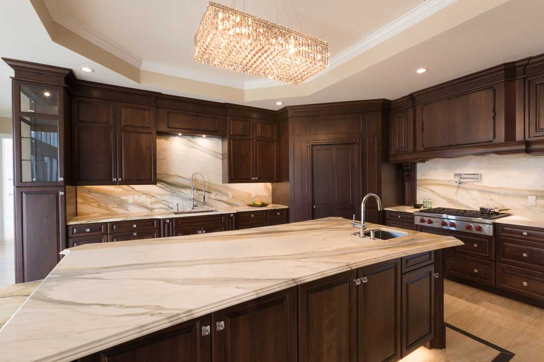 cocoa walnut kitchen design with a large island and marble countertops with matching marble backsplash