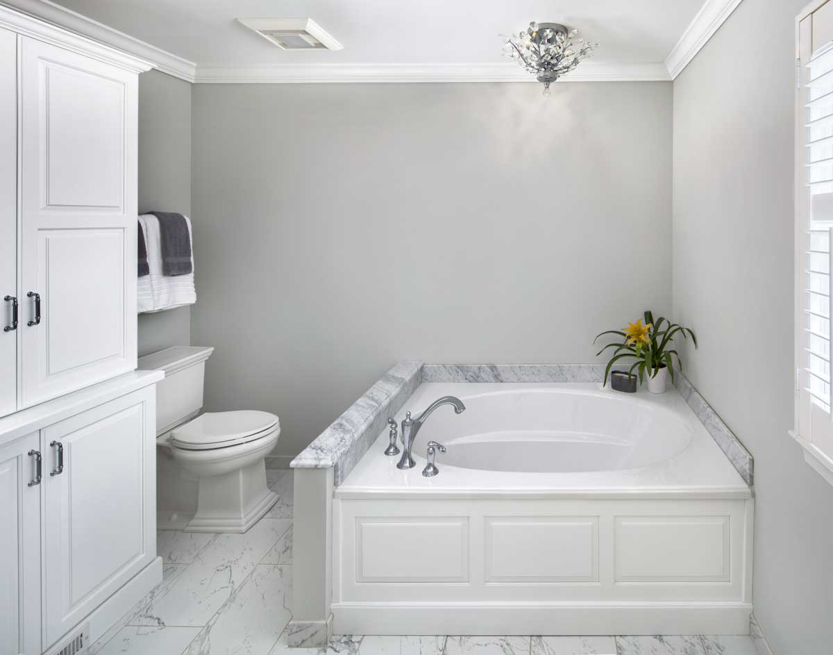 Large white bathtub in a white marble bathroom with yellow color accents and stainless steel fixtures