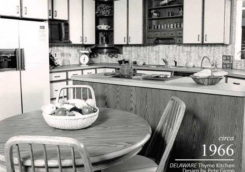 Open shelving and spice storage throughout a vintage kitchen and dining area with a round table