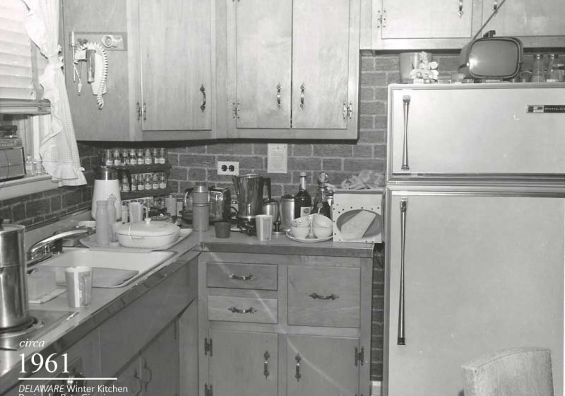 A vintage kitchen full of cooking supplies and a television that rests atop an antique refrigerator
