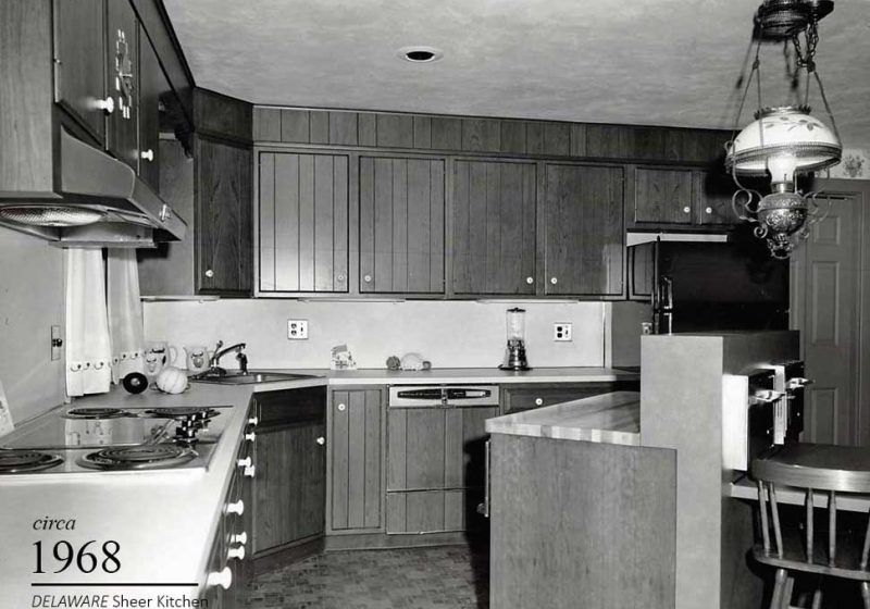 Vintage kitchen in an all white color with dark colored tiles and countertops, built in 1966