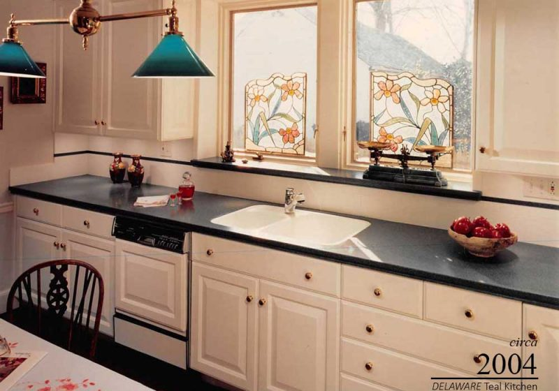 White antique kitchen accented with teal and red colors to promote the homeowner's choice of style