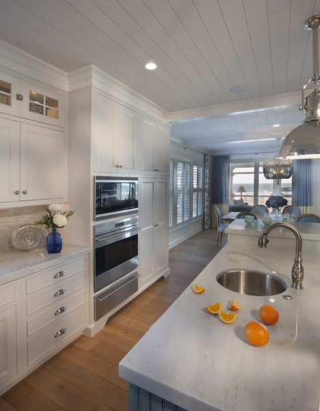 View of traditional kitchen design with multiple food prep areas, baby blue cabinets, and dining space.