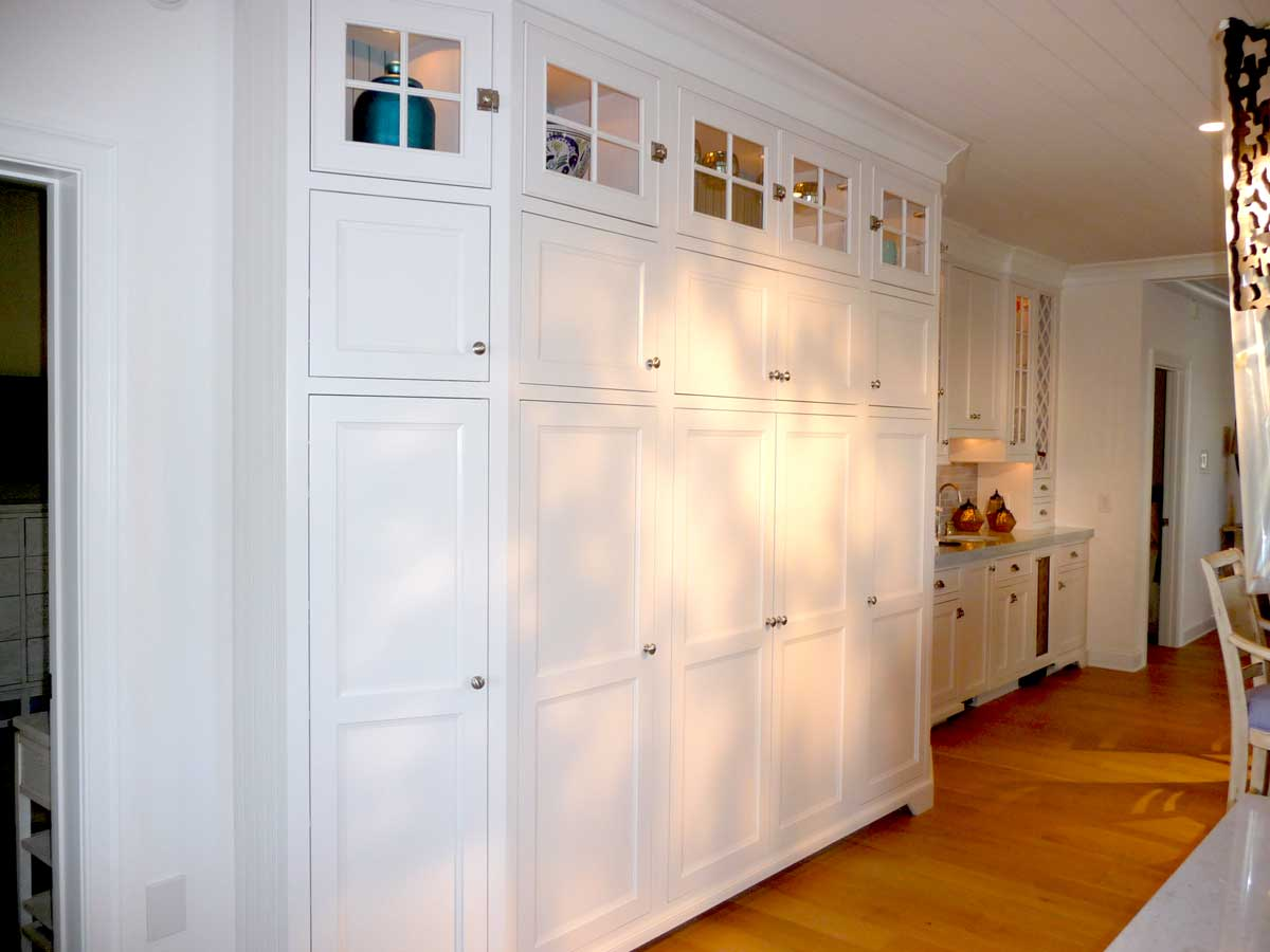Built-in wall cabinetry storage creates organization in large family kitchen space with baby blue cabinets.