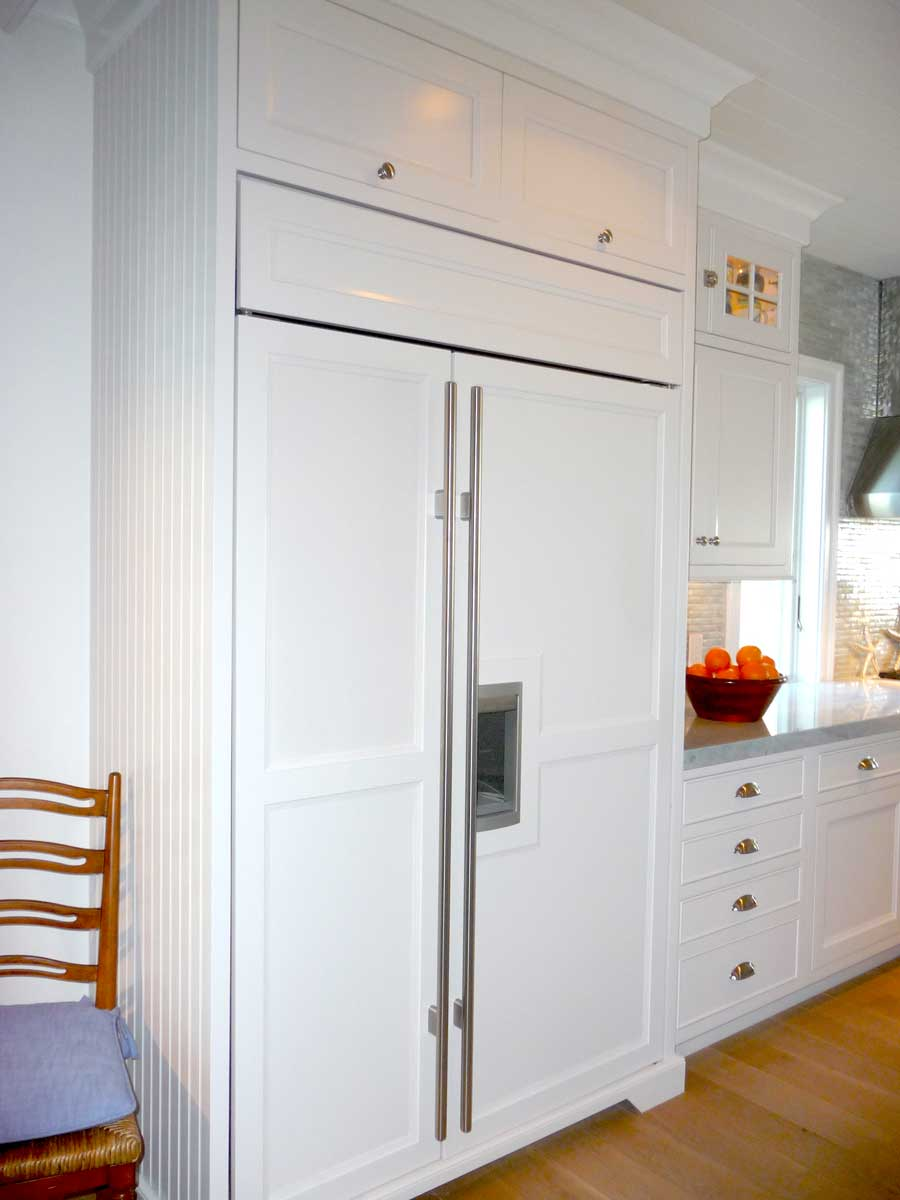 Refrigerator near baby blue cabinets is concealed with white wood paneling to blend with rest of kitchen.