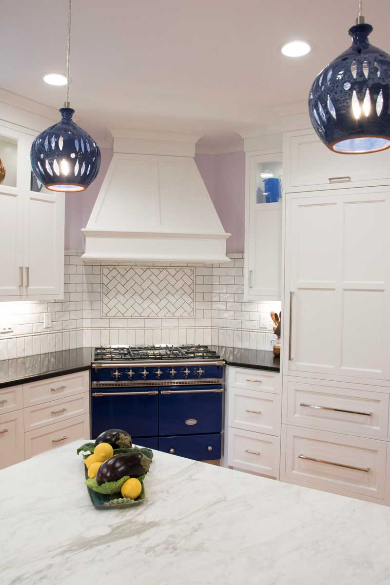 White kitchen cabinetry with black perimeter countertops and calacatta marble peninsula and a Lacanche Range