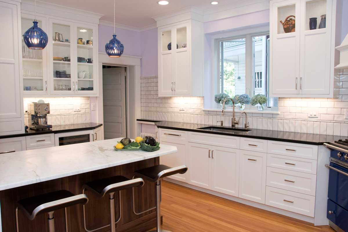 White cabinets with black countertops and marble countertop with dark cabinets with a Lacanche Range