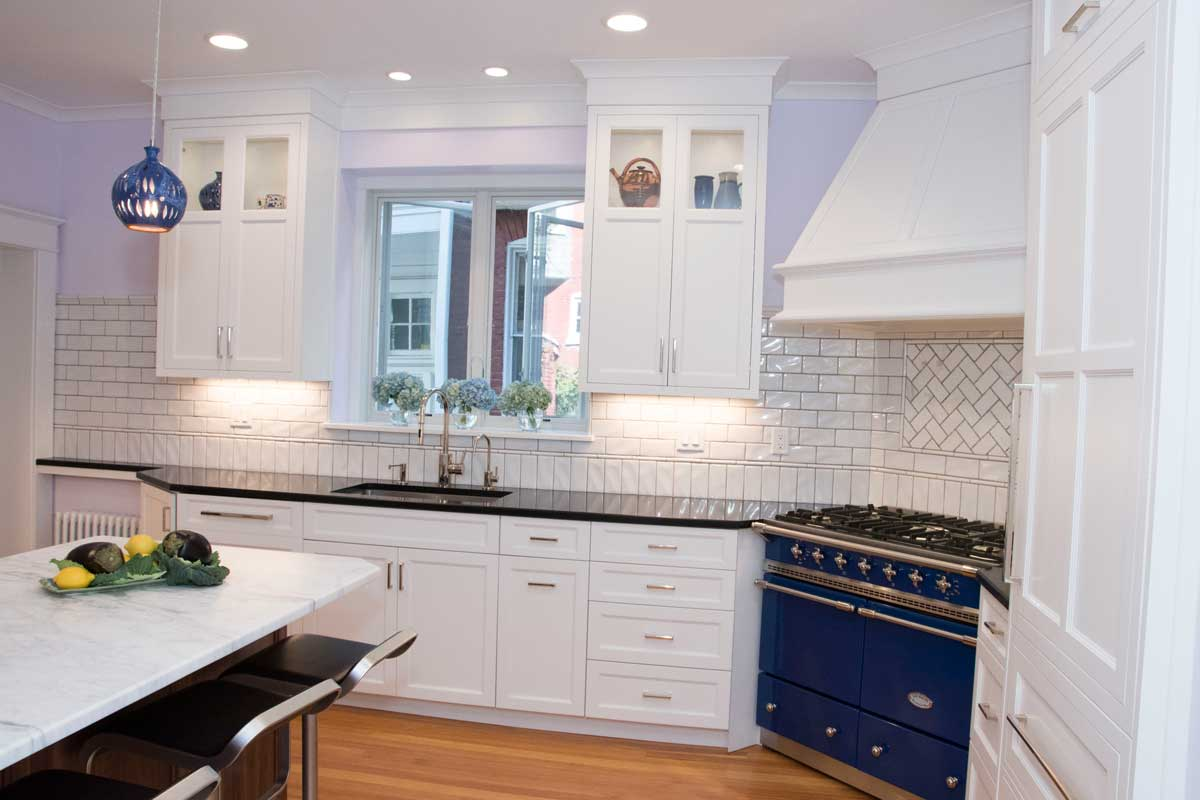 White kitchen cabinetry with subway tile backsplash and a black countertop with a Lacanche Range
