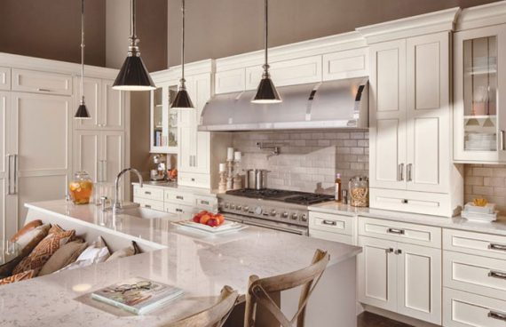 Dura supreme white kitchen cabinetry with a white countertop and stainless-steel appliances and cabinet hardware