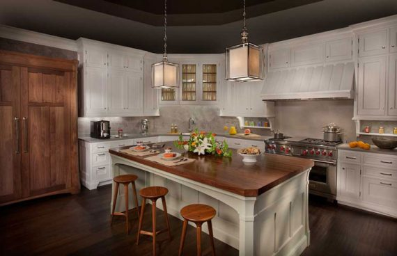 Rutt Handcrafted Cabinetry with a Custom white range hood and custom wood panels for refrigerator doors