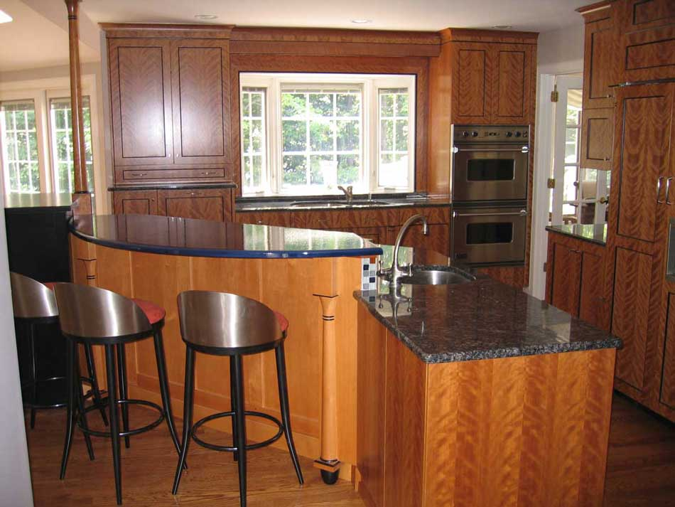 Cherry cabinetry on a kitchen island with granite and pyrolave countertops and a colorful kitchen backsplash