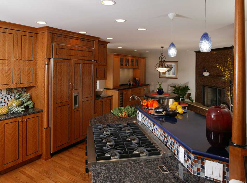 Warm contemporary kitchen design with a multi-level kitchen island with seating and a colorful kitchen backsplash