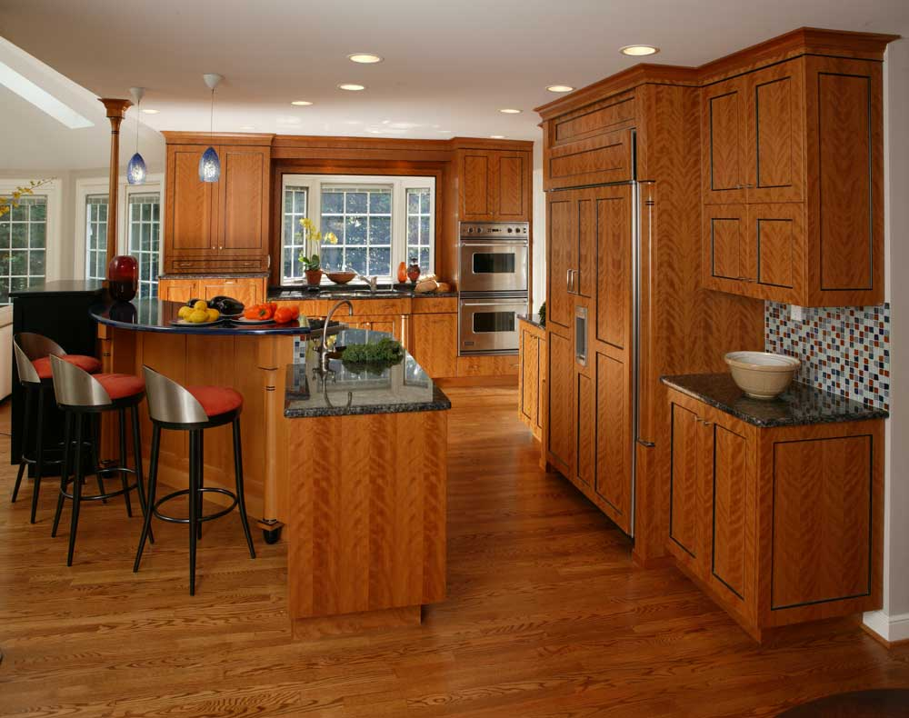 Warm contemporary kitchen design with cherry wood cabinets and a colorful kitchen backsplash and multi-level island