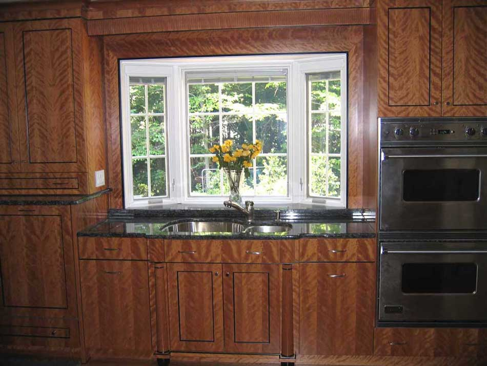 Cherry wood cabinetry with a colorful kitchen backsplash and stainless steel appliances and a bay window